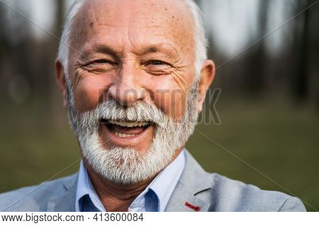 Close Up Portrait Of Happy Senior Man. Elderly Man Is Smiling And Looking At Camera.