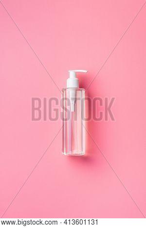 Coronavirus prevention hand sanitizer gel in bottle. Hand disinfectant gel on pink background. Top view.