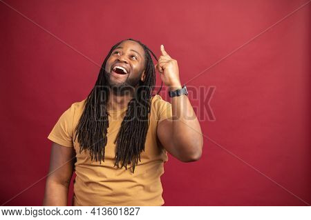 Eureka Concept. African American Man With Dreadlocks Standing Isolated Over Red Background, Pointing