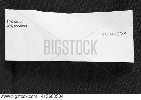 Size Xs And Fabric Composition Clothing Label On Black Textile Background Closeup