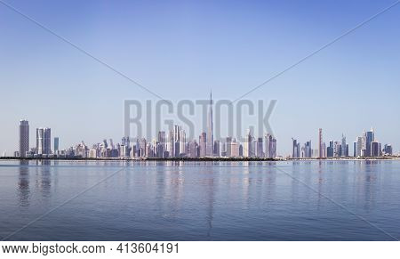 Dubai Downtown Skyline Panorama With Reflections In Dubai Creek, Cold Colors, Seen From Dubai Creek