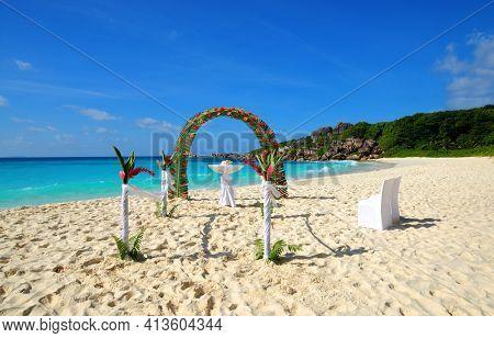LA DIGUE, SEYCHELLES - MARCH 16, 2020 : Beach wedding arch ceremonial decorated with flowers, Grande Anse, La Digue Island, Indian Ocean, Seychelles. Tropical destination.