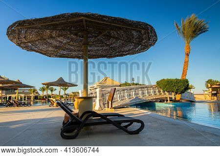 Coral Sea Holiday Resort, Sinai, Egypt - February 19, 2021. Chaise Lounge Under A Wicker Umbrella Ne