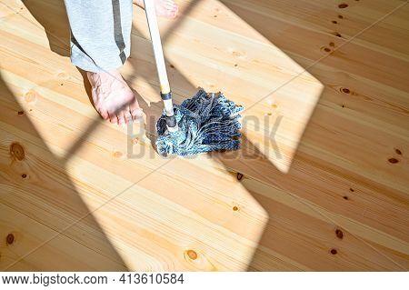 Man Mops Wooden Floor In Sunlight From Window
