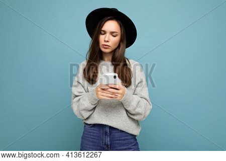 Beautiful Young Brunette Woman Thinking Wearing Black Hat And Grey Sweater Holding Smartphone Lookin