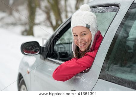 Woman driving in winter on snow covered slippery road in forest