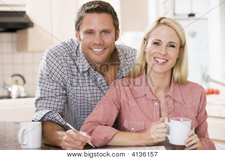 Couples In Kitchen With Newspaper And Coffee Smiling