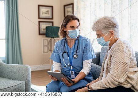Nurse and senior woman going through medical record on digital tablet during home visit and wearing face mask. Doctor wearing protective face mask during covid pandemic and showing medical reports.