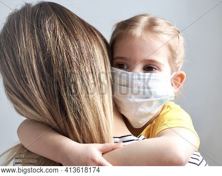 Children And Mother Wearing Mask Protect Covid-19. Little Girl Daughter Hugging Mother On Home Backg