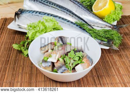 Slices Of Smoked Atlantic Mackerel Fillet With Onion And Vegetable Oil In Bowl Against The Whole Fis