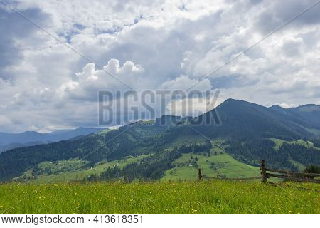 Distant Mountain Ranges Partly Covered With Forests And Fenced Hayfield On A Foreground Against Of C