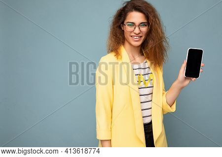 Attractive Smiling Young Woman With Curly Dark Blond Hair Wearing Yellow Jacket And Optical Glasses