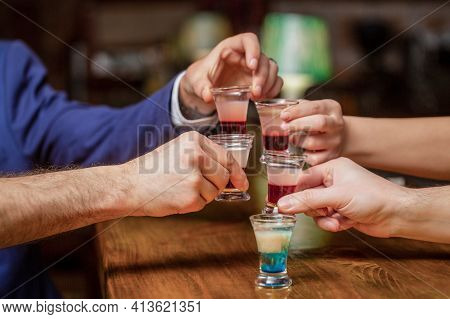 Cocktail At The Nightclub. Group Friends Tequila Shot Glasses In Bar. Male Hands Glasses Of Shot Or