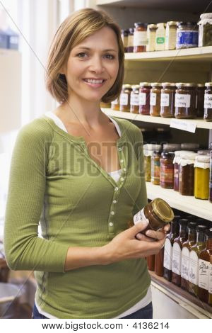 Woman In Market Looking At Preserves Smiling
