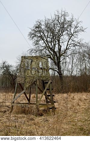 Hunting Tower Covered In Camouflage Net In Springtime