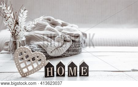 Still Life In Hygge Style With The Wooden Word Home, Decor Details And A Knitted Element. The Concep