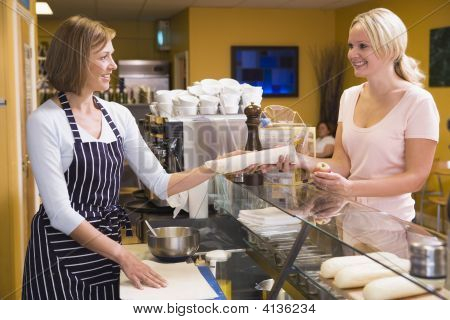 Woman Standing At Counter In Restaurant Serving Customer And Smiling