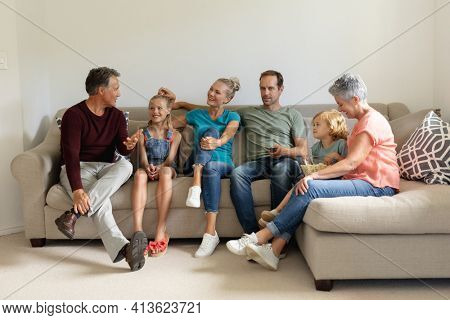 Senior caucasian man sitting on couch talking with his smiling three generation family. happy three generation family spending time together at home.