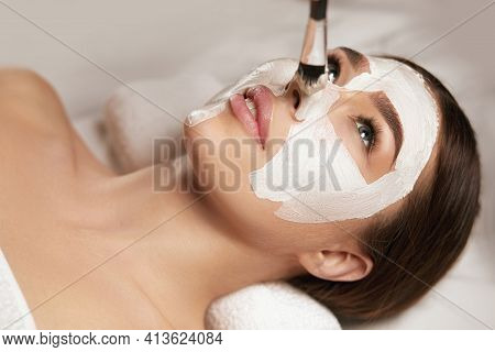 Beautiful Woman With A Clay Mask On Her Face. Facial Peeling Mask. Spa Skin And Body Care. Female Fa