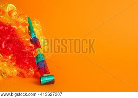 Clown Wig And Party Blower On Orange Background, Space For Text