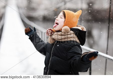 Funny Little Girl Catches Snowflakes In A Beautiful Winter Park During A Snowfall. Cute Baby Is Play