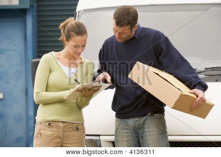 Two Deliverypeople Standing With Van Holding Clipboard And Box