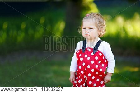 Cute Toddler Girl Playing In Sand On Outdoor Playground. Beautiful Baby In Red Gum Trousers Having F