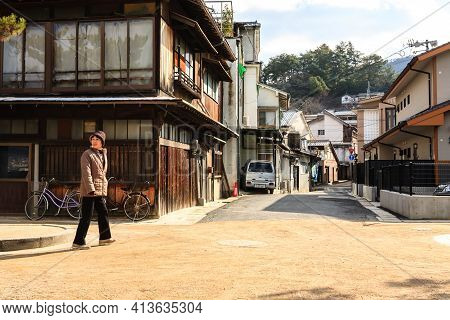 Miyajima, Japan - December 28, 2009: An Elderly Woman Walking Down The Old-fashioned Japanese Street
