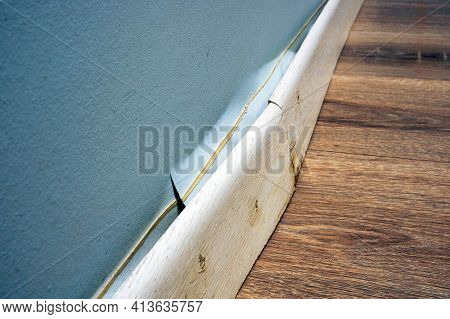 Damaged Skirting Board Detached From The Wall After The Apartment Was Flooded.