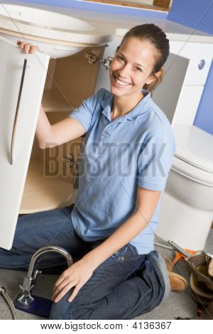 Plumber Working On Sink Smiling