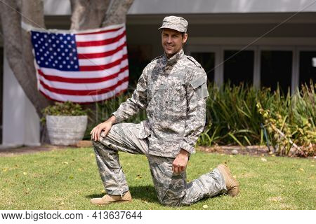 Smiling caucasian soldier father kneeling in garden with american flag hanging outside house. soldier returning home to family.