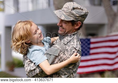 Smiling caucasian soldier father carrying son in garden with american flag hanging outside house. soldier returning home to family.