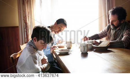Angry Small Girl With Parents Sulking Indoors At The Table At Home, Poverty Concept.