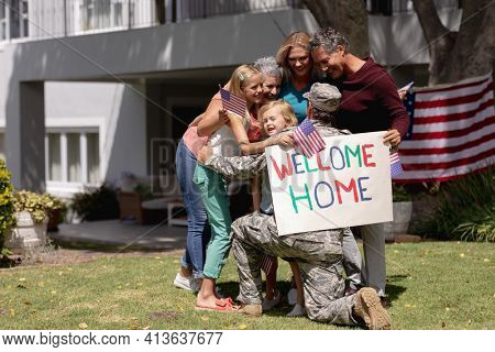 Happy caucasian soldier father embracing wife, children and parents outside home with welcome sign. soldier returning home to family.