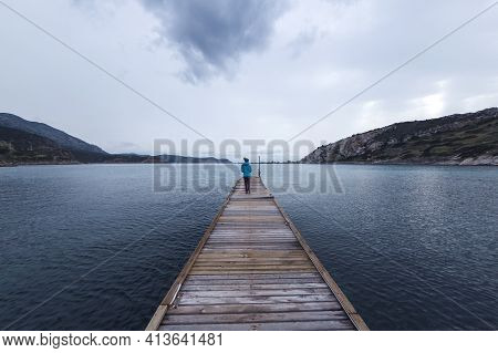 A Girl Stands On The Pier And Looks At The Sea, A Woman Stands In The Middle Of The Pier, A Trip To