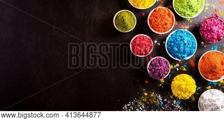 Happy Holi Festival Decoration.top View Of Colorful Holi Powder On Dark Background.