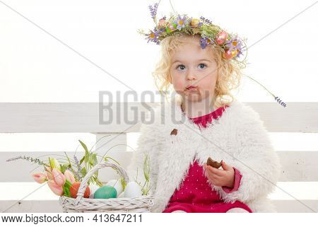 easter flower child eating chocolate eggs in easter