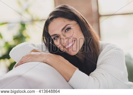 Photo Of Funny Woman Sit Couch Relax Shiny Smile Look Camera Wear Specs White Pullover In Living Roo