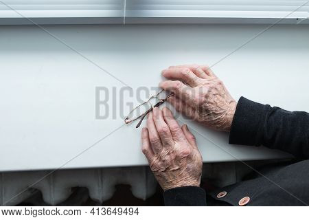 Elderly People Suffering From Loneliness. An Elderly Woman's Hands Are Holding Glasses On The Window