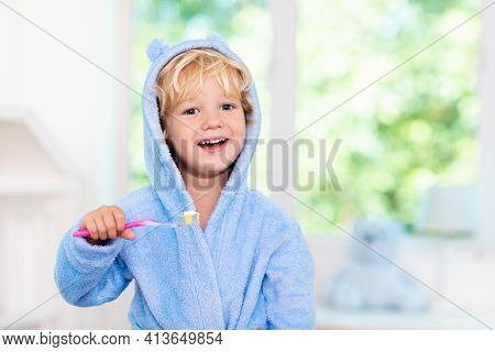 Child Brushing Teeth. Kids Tooth Brush And Paste. Little Baby Boy In Blue Bath Robe Or Towel Brushin