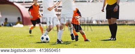 Running Football Players. School Soccer Teams Compete In Tournament Match. Young Football Players An
