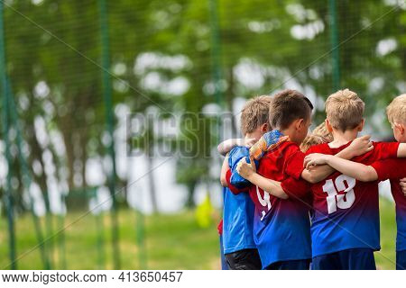 Happy Children Huddling In A Team On Sports Field. Group Of School Boys Standing Together In A Circl