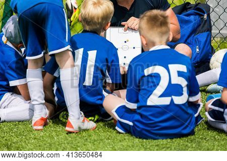 Sports Coach Teaching School Boys On Summer Day. Young Soccer Trainer Coaching Kids Using Tactics Bo