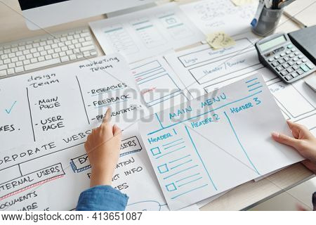 Ux Designer Analyzing Layouts In Front Of Him When Creating Layout Of Website Interface Of New Compa