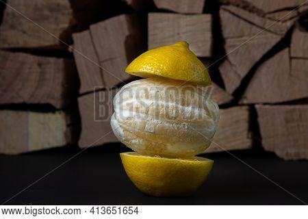 Lemon On A Dark Background. Peeled Lemon On A Wooden Background. Creative Photo Of Lemon.