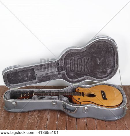 Musical Instrument - Broken Acoustic Guitar In Hard Case On A White Wall Background And Wooden Floor