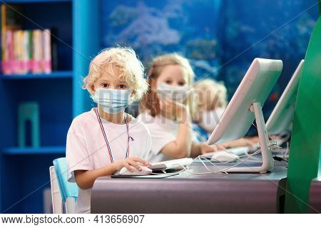 Kids In Face Mask With Computer. Children Learning And Studying Information And Communications Techn