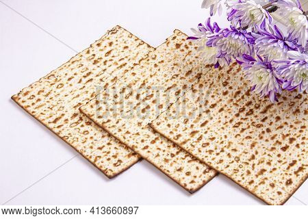 Passover Background With Matzah And White And Purple Chrysanthemums. Jewish Holiday. View From Above