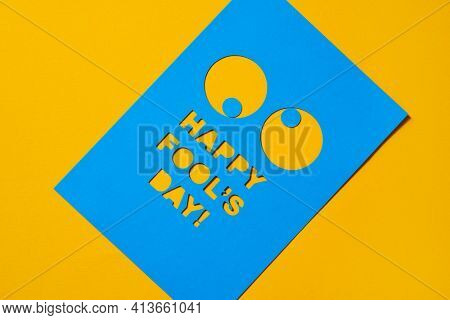 the text happy fools day and a pair of funny eyes cut out in a blue paperboard, against an orange background