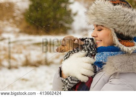 Young Woman Wrapped Her Best Friend Little Dog In Warm Blanket Scarf To Warm Him In Cold Snowy Winte